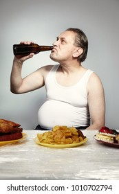Aging man in a-shirt eating lot of junk food and beer