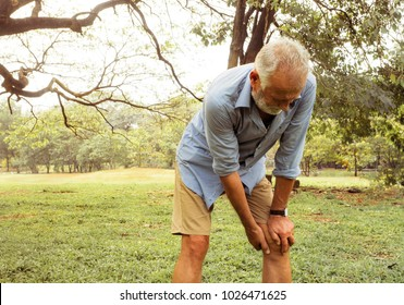 Aging man having pain in his knee on the park, Pain In The Elderly, Health care