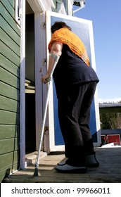 Aging, overweight disabled woman with crutch entering her shabby old house.