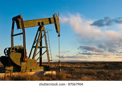 """Aging pump rig standing alone against the prairie of western colorado, """"sunset on oil"""" depicts the fading fossil fuel extraction industry today."""