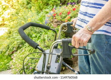 Aging woman's on hand holding on to the handle of an adult walker with brake handles, select focus. In the garden