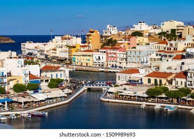 AGIOS NIKOLAOS, CRETE, GREECE - 12 September 2019: Lake Voulismeni and various colorful buildings in Agios Nikolaos seen at sunset, East Crete, Greece