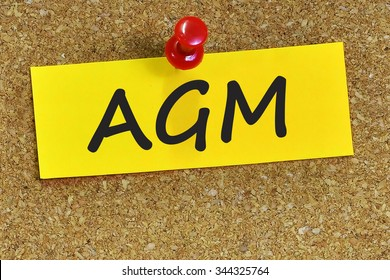 AGM word on yellow notepaper with cork background.