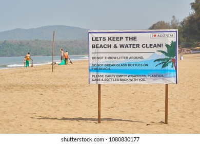 Agonda, Goa / India - 04 01 2018: A sign regarding trash on the beach in Agonda with people in the back cleaning the beach.