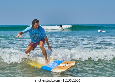 Agonda, Goa / India - Feb 25 2018: A surfing student from Aloha Surf India catching a wave on a clear beautiful day at Agonda Beach