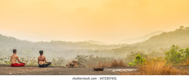 Agonda, Goa / India - March 04 2018: A man and a woman sitting in yoga meditation in front of a sunrise over a valley in south Goa