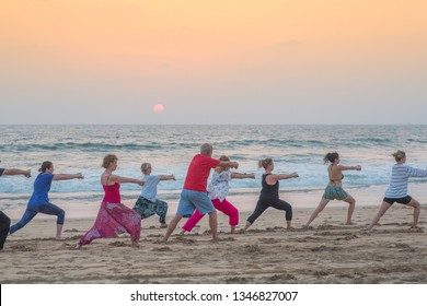 Agonda, Goa / India - March 19 2019 - A group of people performing Tai Chi at the beach at sunset.