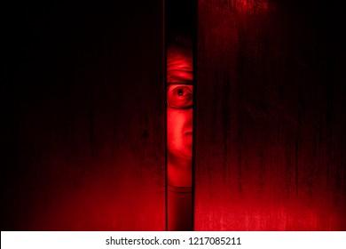 Agoraphobia concept / eye peeking behind the door