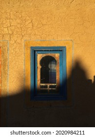 Agoudal, Atlas Mountains, Morocco, November 2019: Detail of blue modish style window on amber yellow wall on traditional Moroccan adobe house in Atlas Mountains with shadow of tree projected on it