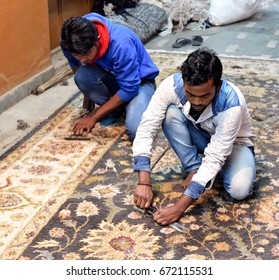 AGRA - February 11, 2017:Indian man performs traditional carpet trimming. Some of the most impressive examples of paramount workmanship on antique rugs are seen on rugs made in Agra, India