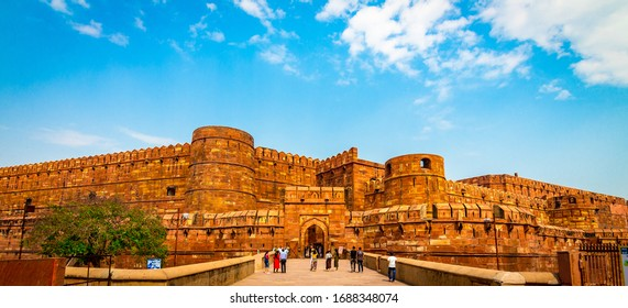 Agra Fort - Historic red sandstone fort of medieval India on bright sunny day. Agra Fort is a UNESCO World Heritage site in the city of Uttar Pradesh India. Tourists at entrance to Agra Fort. - Image