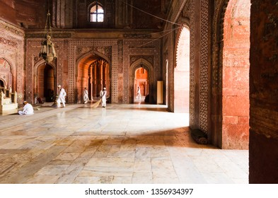 AGRA, INDIA - 5 MAY 2015: Mosque workers sweeping the marble floor of the main prayer hall in the Taj Mahal masjid, Agra, India.