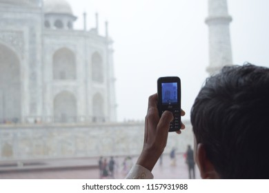 Agra / India - August 15 2018: A man taking pictures of taj mahal from his JIO phone digital india