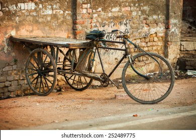 AGRA, INDIA - CIRCA NOV 2012: An improvised tricycle with a wooden cargo pallet, parked against an old brick wall in Agra, India.