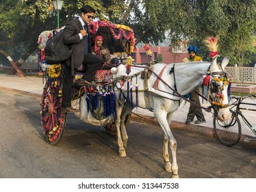 Agra, India - December 10, 2014: A guy on the work takes a lift from a man, in very colorful tonga, on the road in Agra on a cold December morning with an onlooker on the side.