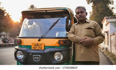 Agra, India - December 12, 2018: Indian auto rickshaw tut-tuk driver man recounts money.