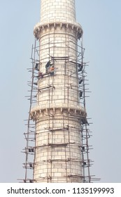 AGRA, INDIA - JANUARY 13, 2015 : Craftsmen on a high scaffold repairing the marble facade of the north east minaret at the Taj Mahal.