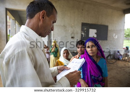 AGRA, INDIA, JULY 18: Indian doctor consulting a patient medical note. Medical free treatment provided by Pushpanjali Fair Trade Organization project. India 2013. (Selective focus)