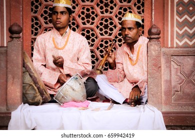 AGRA, INDIA - JUNE 5, 2013: Two musicians sit in front of a decorative red wall wearing matching clothing outside the Taj