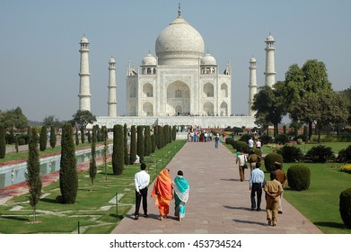 AGRA, INDIA - MARCH 07, 2006: People walking through the gardens outside of the mausoleum of the Taj Mahal, built of white marble , in the city of Agra , Utta Pradesh province of India