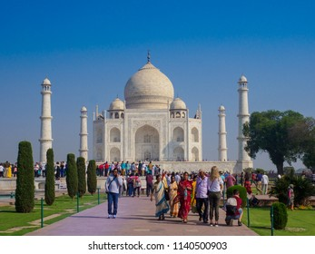 Agra, India - March 11, 2018:  Tourists visiting Taj Mahal, an ivory-white marble mausoleum. It was commissioned in 1632 by the Mughal emperor, Shah Jahan, to house the tomb of his queen, Mumtaz Mahal