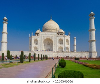 Agra, India - March 11, 2018:  Tourists visiting the Taj Mahal, the ivory-white marble mausoleum. It was commissioned in 1632 by the Mughal emperor, Shah Jahan, to house the tomb of his queen.