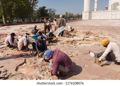 Agra India - March 11, 2018: Workers manually repairing the outside ground of Taj Mahal, the famous ivory-white marble mausoleum in Agra, India.