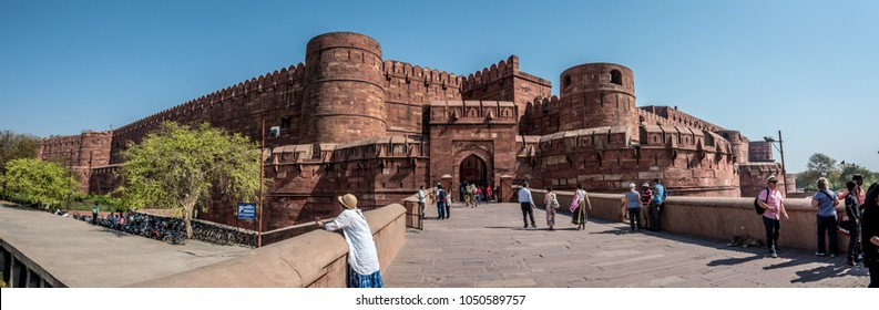 AGRA, INDIA - March 13, 2018: Front Gate and Towers of Fort Agra India with Tourists Walking on the front Walkway Sidewalk