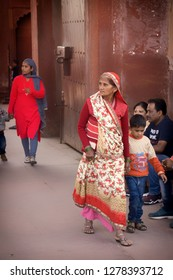 AGRA, INDIA - November 24, 2018: Woman of certain age dressed in traditional indian costume walking by with a kid in Red Fort.