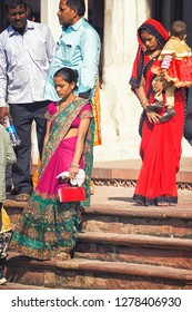 AGRA, INDIA - November 24, 2018: two young ladies wearing traditional indian dresses walking down the stairs in red fort with baby.