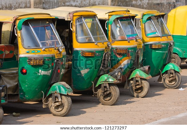 AGRA, INDIA - NOVEMBER 26: Auto rickshaw taxis on a road on November 26, 2012 in Agra, India. These iconic taxis have recently been fitted with CNG powered engines in an effort to reduce pollution