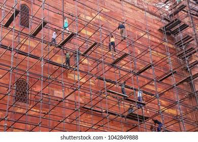 AGRA, INDIA - NOVEMBER 8: Unidentified people build scaffolding on the wall of Taj Mahal complex on November 8, 2014 in Agra, India. Agra is one of the most populous cities in Uttar Pradesh