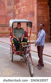 AGRA, INDIA - NOVEMBER 8: Unidentified man stands by his pedicab with a passenger in Taj Ganj neighborhood on November 8, 2014 in Agra, India. Agra is one of the most populous cities in Uttar Pradesh
