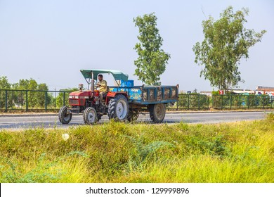 AGRA, INDIA - OCT 25: A tractor with trailer on highway on October 17, 2013 in Agra, India. Agriculture contributes 21 percent of India??s GDP,the rural areas are home to some 72 percent of the Indians people.