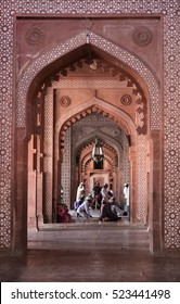 Agra, India - October 12: Muslims praying inside the red sandstone doorway and hall of the fort Jama Masjid Friday Mosque on October 12, 2016 in Fatehpur Sikri, Agra, India.