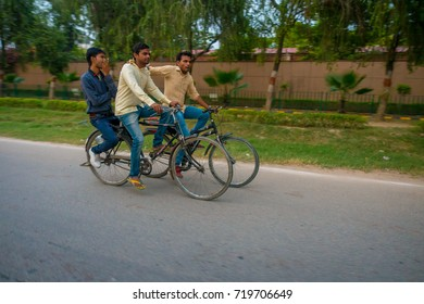 AGRA, INDIA - SEPTEMBER 19, 2017: Unidentified men ride bikes in the streets in central India in Agra, India