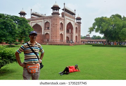 Agra, Uttar Pradesh, India, 19th August, 2018: Two men posing in front of  main entrance gate of Taj Mahal of Agra, (Darwaza-i-rauza) with green field and trees, selective focusing