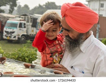 Agra, Uttar Pradesh/ India - August 12 2019: view of a sikh man with his grand son bow their head in the Sikh Gurudwara in Agra