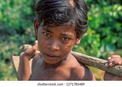 Agra, Uttar Pradesh / India - November 1998: a close-up portrait of a shirtless Indian boy with a hoe on his shoulders during a work break, the sweat beaded on the forehead, blurred background