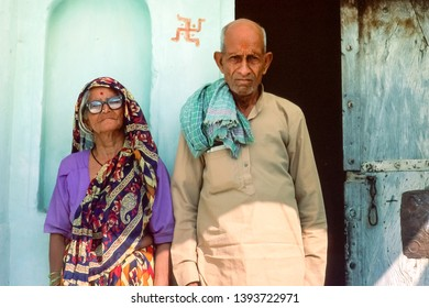 Agra, Uttar Pradesh/ India - November 1998: portrait of an elderly couple, traditional clothing, standing at the door in front of their house, religious symbol painted on the wall