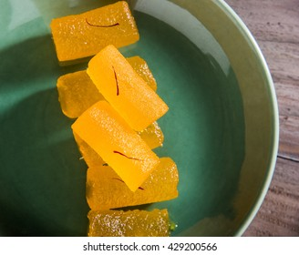 Agra's Shahi kesar Petha - is a sweet candy made using Pumpkin Pieces dipped in sugar syrup with saffron toppings. Served in a plate over moody background. selective focus