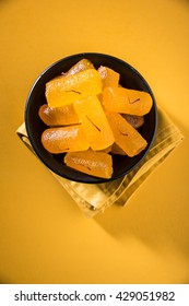 Agra's Shahi Petha - is a sweet candy made using Pumpkin Pieces dipped in sugar syrup with saffron toppings. Served in a plate over moody background. selective focus