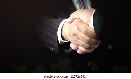 Agree concept: Two businessman handshake on dark room background