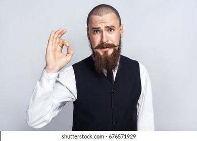 Agree. Handsome businessman with beard and handlebar mustache looking at camera with Ok sign. studio shot, on gray background.