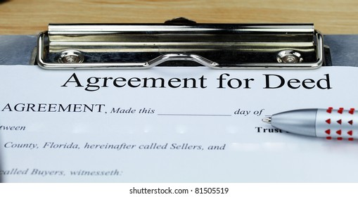 An agreement for a deed document on a clip board with a pen, ready for the client to complete.