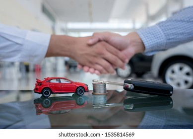 Agreements to buy new cars, new car loans or signing contracts with car keys and money in the foreground Blurred background for two business people standing hand in hand