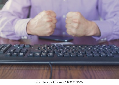 Agression in the Internet, man sitting behind keyboard with hands clenched into a fists