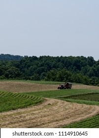 Agricultural background of a dairy farmer harvesting haylage on rolling hill fields in Appalachia - verticle