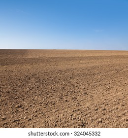 Agricultural background with plowed field and clear blue sky