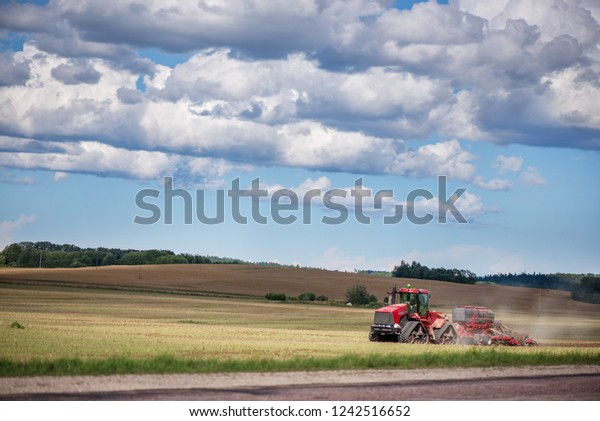 Agricultural background with red tractor pulling plow, throwing dust in air. Combine harvester at wheat field. Heavy machinery during cultivation, working on fields. Dramatic sky, rain, storm clouds